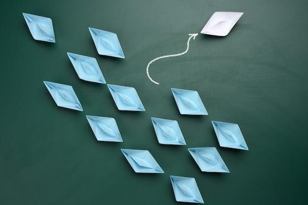 Een groep blauwe papieren boten vaart in de ene richting, een witte vaart in de tegenovergestelde richting. het concept van een buitengewone persoonlijkheid, handelen in strijd met de fundamenten van de samenleving