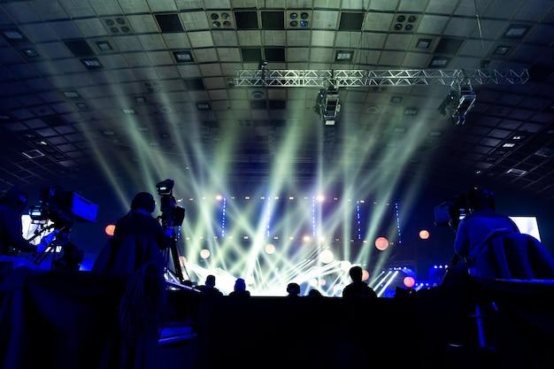 Een groep cameramannen aan het werk tijdens het concert. televisie-uitzending evenement. silhouetten van arbeiders tegen de achtergrond van kleurrijke balken.