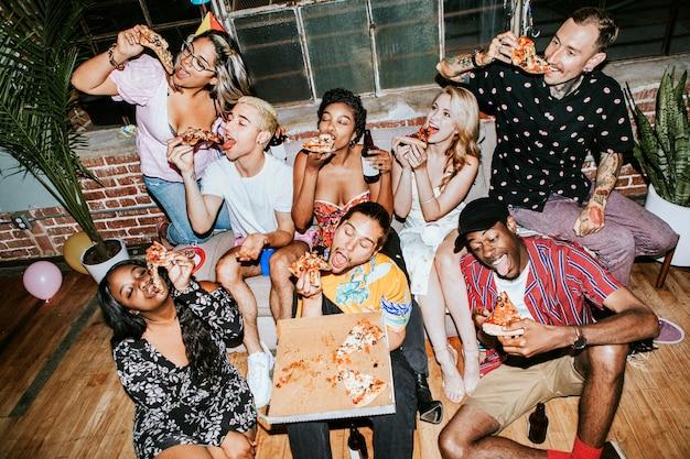 Een groep diverse vrienden die op een feestje van pizza genieten