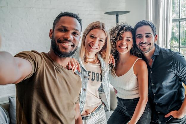 Een groep diverse vrienden die plezier hebben terwijl ze samen selfies maken. vrienden concept.