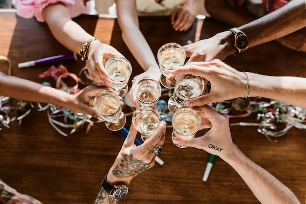 Een groep diverse vrienden die proosten op een feestje