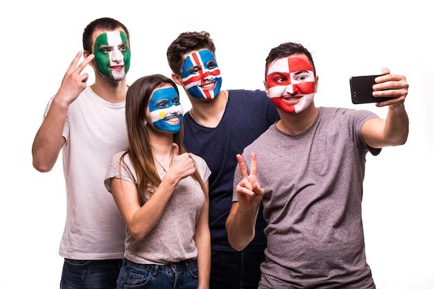 Een groep fans ondersteunt hun nationale teams met geschilderde gezichten. argentinië, kroatië, ijsland, nigeria fans nemen selfie op telefoon geïsoleerd op een witte achtergrond