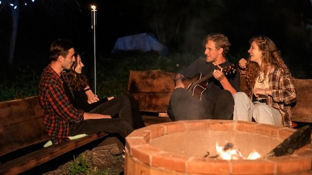 Een groep gelukkige jonge vrienden bij een kampvuur bij glamping, nacht. twee mannen en vrouwen. gitaar spelen