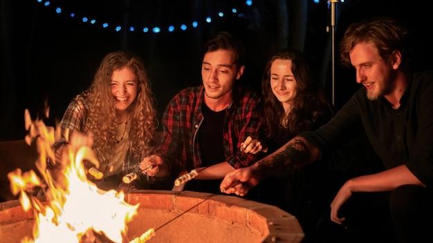 Een groep gelukkige jonge vrienden bij een kampvuur op glamping-avond