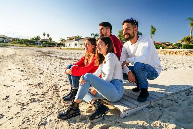 Een groep gelukkige jonge vrienden die in de natuur reizen, bogen zich voorover en zittend op een houten promenade