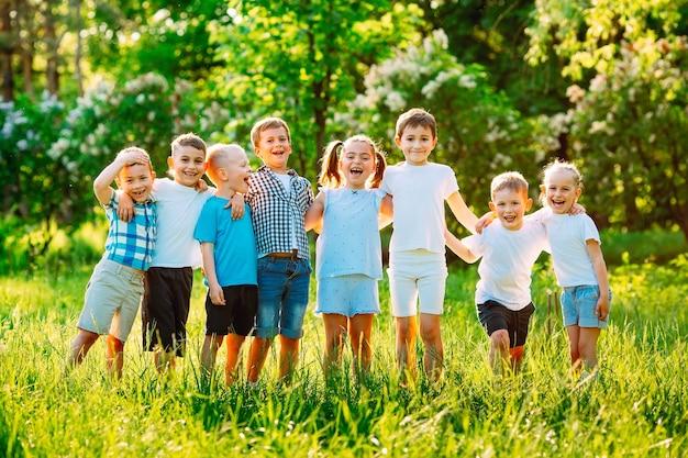 Een groep gelukkige kinderen van jongens en meisjes rennen op een zonnige zomerdag in het park op het gras.