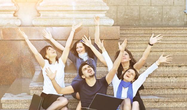 Een groep gelukkige studenten steekt hun hand op van vreugde bij zonnig weer