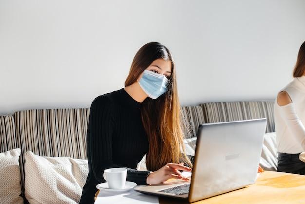 Een groep gemaskerde meisjes houdt een sociale afstand in een café wanneer ze op laptops werken