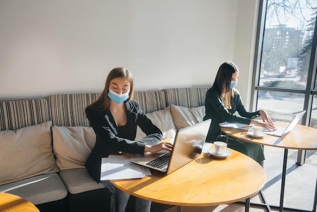 Een groep gemaskerde meisjes houdt in een café een sociale afstand wanneer ze op laptops werken.