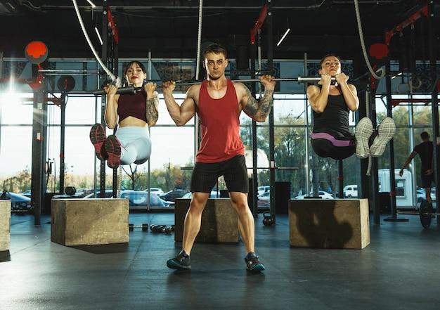 Een groep gespierde atleten die trainen in de sportschool. gymnastiek, training, flexibiliteit voor fitnesstraining. actieve en gezonde levensstijl, jeugd, bodybuilding. bovenlichaam trainen met gewicht, teamwork.