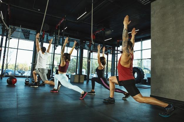 Een groep gespierde atleten die trainen in de sportschool. gymnastiek, training, flexibiliteit voor fitnesstraining. actieve en gezonde levensstijl, jeugd, bodybuilding. trainen in lunges en rekoefeningen