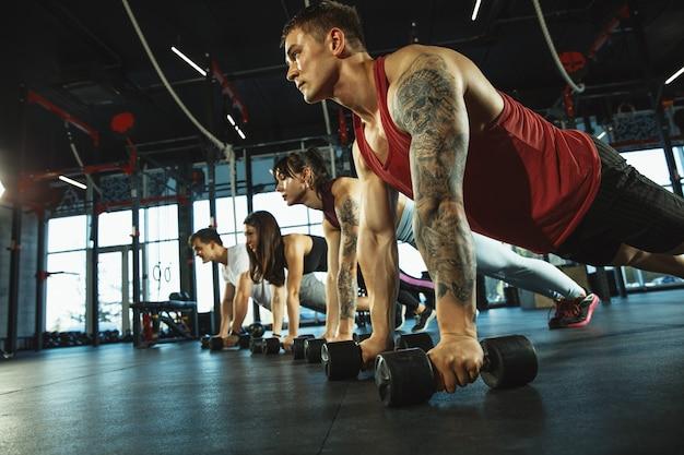 Een groep gespierde atleten die trainen in de sportschool. gymnastiek, training, flexibiliteit voor fitnesstraining. actieve en gezonde levensstijl, jeugd, bodybuilding. trainen in oefeningen met gewichten.