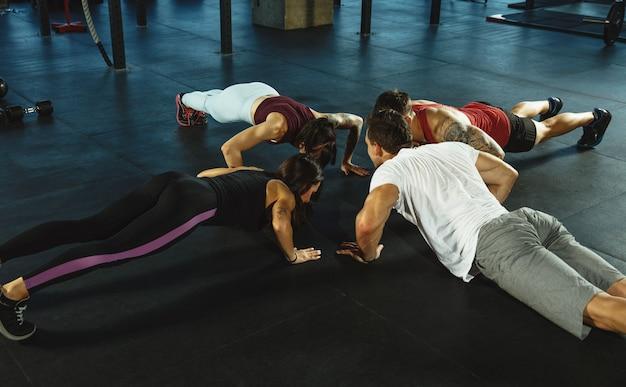 Een groep gespierde atleten die trainen in de sportschool. gymnastiek, training, flexibiliteit voor fitnesstraining. actieve en gezonde levensstijl, jeugd, bodybuilding. trainen in stretching en plank.