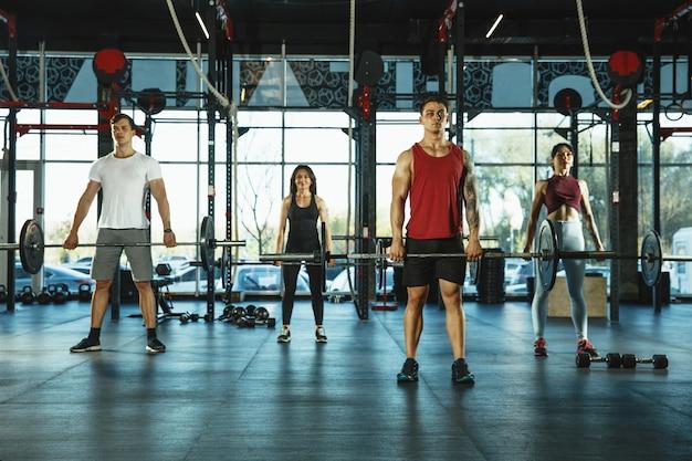 Een groep gespierde atleten die trainen in de sportschool. gymnastiek, training, flexibiliteit voor fitnesstraining. actieve en gezonde levensstijl, jeugd, bodybuilding. trainen met gewichten, squats doen.