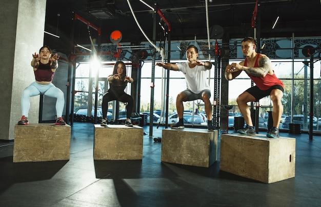 Een groep gespierde atleten die trainen in de sportschool. gymnastiek, training, flexibiliteit voor fitnesstraining. actieve en gezonde levensstijl, jeugd, bodybuilding. trainen met sportieve springboxen.