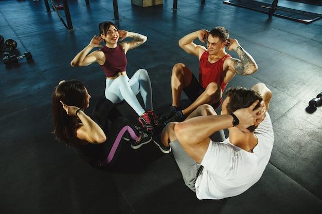 Een groep gespierde atleten die trainen in de sportschool. gymnastiek, training, flexibiliteit voor fitnesstraining. actieve en gezonde levensstijl, jeugd, bodybuilding. training in crunches of buikspieren, bovenaanzicht.