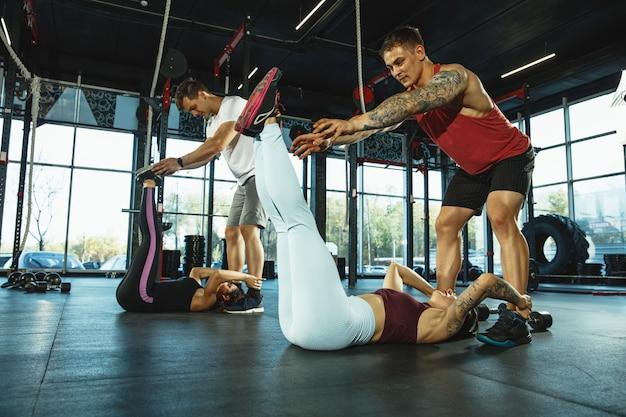 Een groep gespierde atleten die trainen in de sportschool gymnastiektraining fitnesstraining