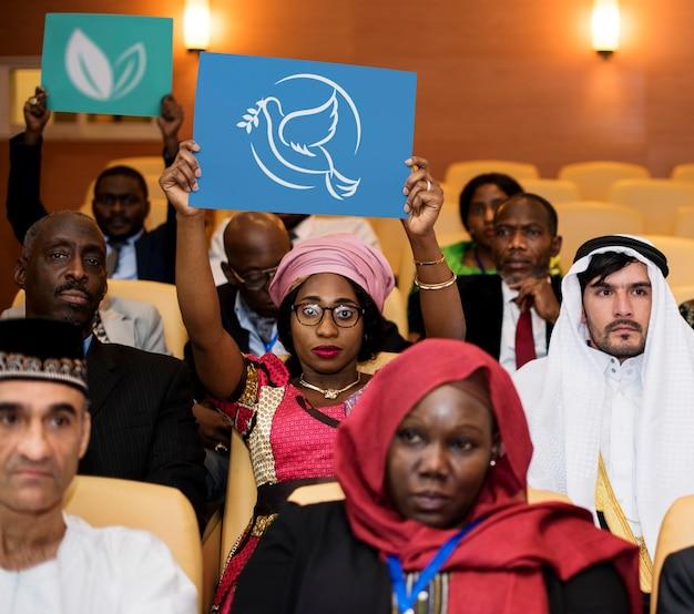 Een groep internationale afgevaardigden toont het symbool van vrede en milieu