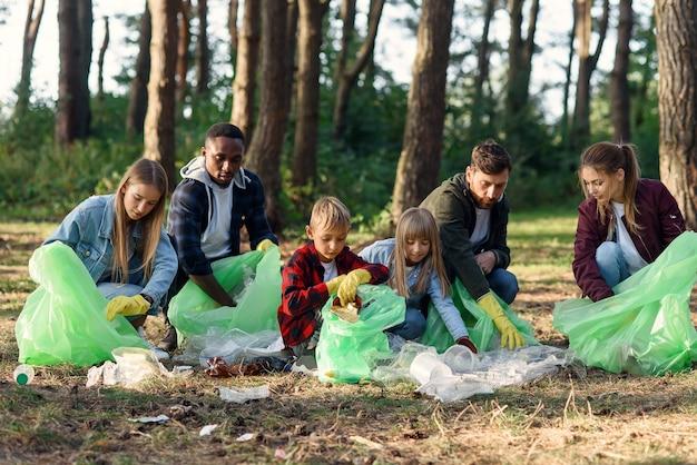 Een groep internationale vrijwilligers van meerdere leeftijd houdt de natuur schoon en haalt vuilnis op uit het bos. ecologie concept.