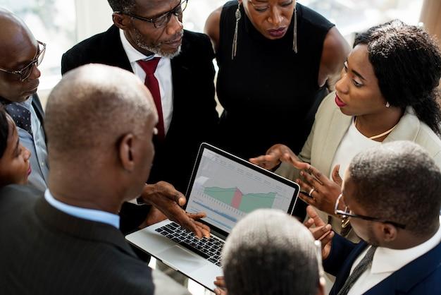 Een groep internationale zakenmensen hebben een discussie met een laptop