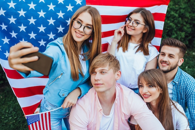 Een groep jonge amerikanen die selfie met amerikaanse vlag doen.