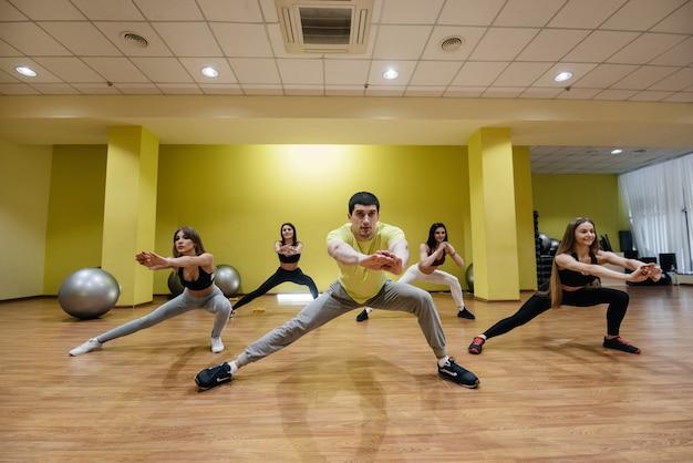 Een groep jonge atletische meisjes voert onder begeleiding van een coach oefeningen uit in de sportschool. gezonde levensstijl