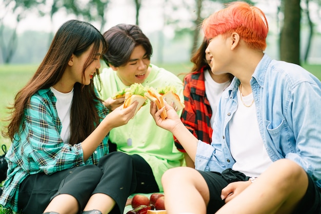 Een groep jonge aziaten die vrolijk broodjes eten in het park