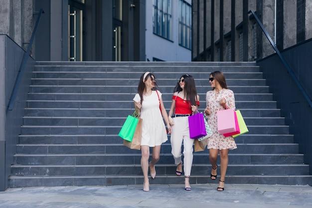 Een groep jonge gelukkige mooie tienermeisjes in vrijetijdskleding, top en broek die van het winkelcentrum met kleurzakken in handen lopen. succesvol winkelen. trappen en winkelcomplex op de achtergrond