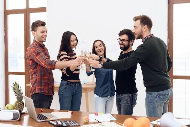 Een groep jonge kantoormedewerkers vieren.