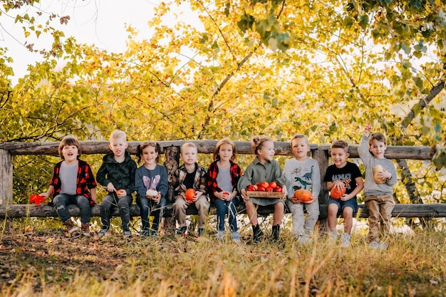 Een groep jonge kinderen met pompoenen in hun handen die op een houten omheining zitten