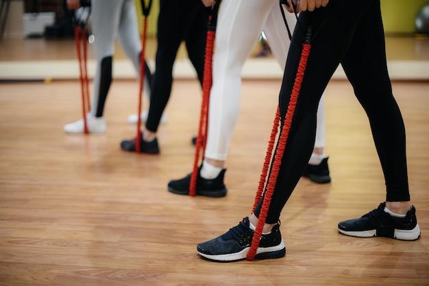 Een groep jonge meisjes houdt zich bezig met fitness met een expander onder begeleiding van een ervaren coach. fitness, gezonde levensstijl.