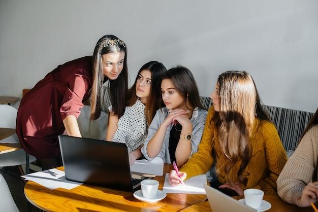Een groep jonge meisjes zit in een kantoor achter computers en bespreekt projecten. communicatie en training online.