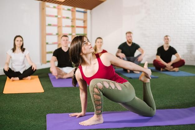 Een groep jonge mensen die joga-oefeningen binnenshuis doen in de sportschool