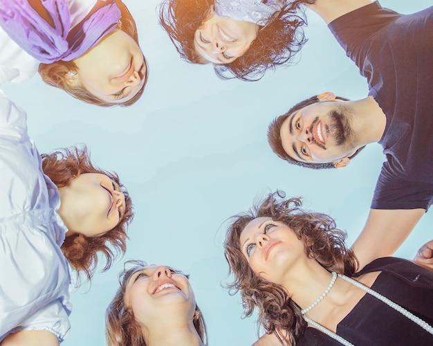 Een groep jonge mensen in een cirkel in de lucht kijken naar elkaar