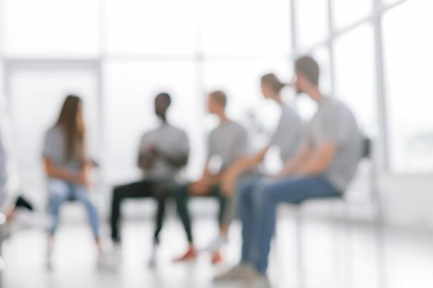 Een groep jonge mensen tijdens een bijeenkomst in een vergaderruimte