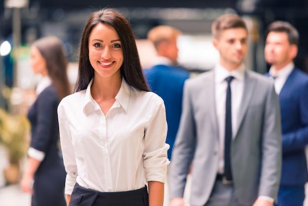 Een groep jonge mensen uit het bedrijfsleven glimlachen.