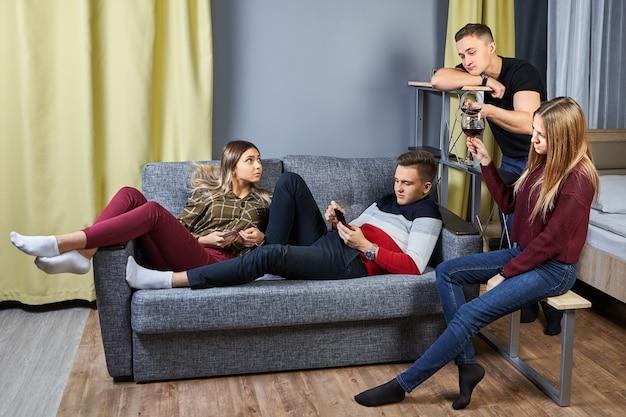 Een groep jonge mensen van twee vrouwen en een paar mannen, in de studententijd, rust uit in een appartement of slaapzaal, na een dag hard werken of studeren.