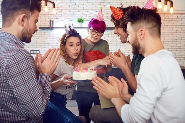 Een groep jonge mensenstudenten met verjaardagstaart viert binnen.