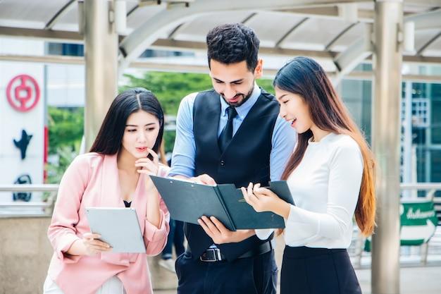 Een groep jonge, multi-etnische jongeren kijkt graag naar een map
