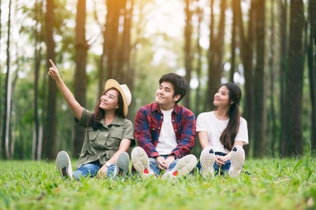 Een groep jonge reizigers die op een groen gras zitten en een prachtig dennenbos inkijken