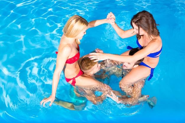 Een groep jonge vrienden die plezier hebben in een zwembad.