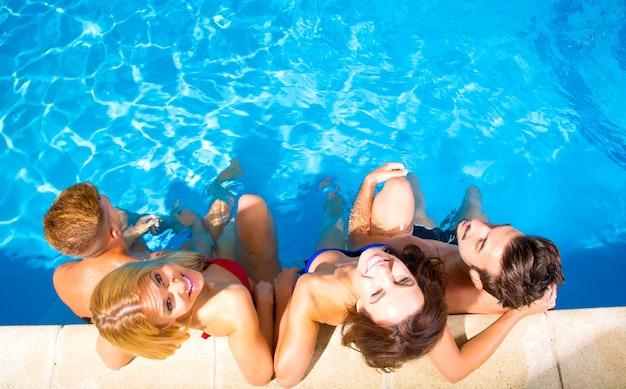 Een groep jonge vrienden die samen in een zwembad ontspannen.