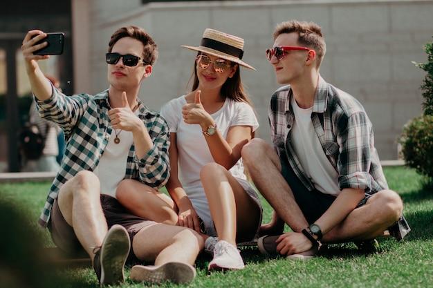 Een groep jonge vrienden selfies maken een duim omhoog op het zonnige gazon