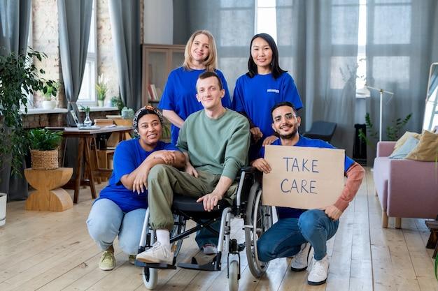 Een groep jonge vrijwilligers in uniform en gehandicapte man