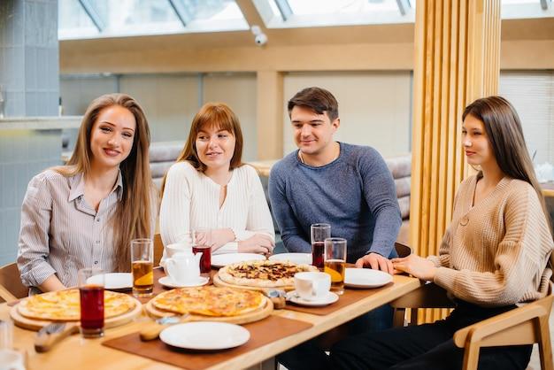 Een groep jonge vrolijke vrienden zit in een café te praten en pizza te eten. lunchen bij de pizzeria.