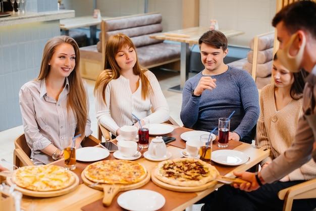 Een groep jonge vrolijke vrienden zit in een café te praten en pizza te eten