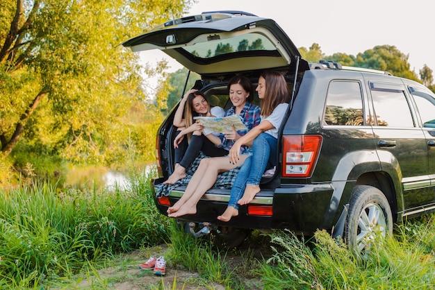 Een groep jonge vrolijke vrouwen reist met de auto door de natuur