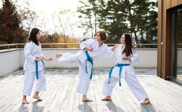 Een groep jonge vrouwen die buiten op het terras karate beoefenen.