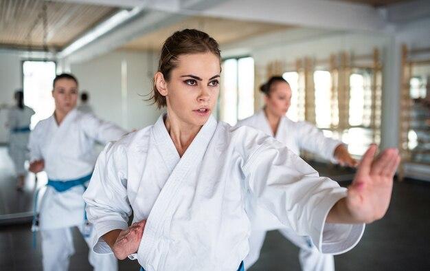 Een groep jonge vrouwen die karate binnenshuis beoefenen in de sportschool.