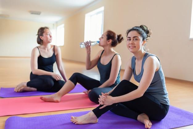 Een groep jonge vrouwen rusten op matten na de training